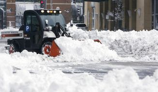 A Rochester Municipal Parking crew clears snow around the First Street Ramp in downtown Rochester, Minn., on Friday, Feb. 24, 2017.   Forecasters expected additional snow through Friday night. The heavy snow missed the Twin Cities in Minnesota and the Milwaukee metro area in Wisconsin. (Andrew Link/The Rochester Post-Bulletin via AP)