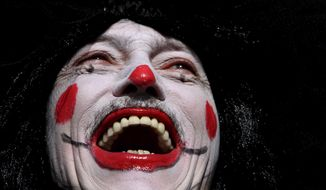 """A clown-faced reveler smiles wide as he takes part in the """"Galo da Madrugada"""" or the Morning Rooster carnival parade, in downtown Recife, in the Brazilian state of Pernambuco, Saturday, Feb. 25, 2017. The """"Galo da Madrugada"""" took to the streets for the first time in 1975 with the aim of rescuing the traditional carnival of Recife. It is now considered one of the largest carnival parades. (AP Photo/Eraldo Peres)"""