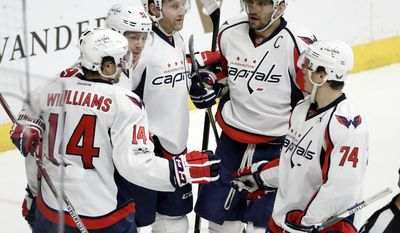 Washington Capitals center Evgeny Kuznetsov (92), of Russia, celebrates with Justin Williams (14), Karl Alzner (27), Alex Ovechkin (8), also of Russia, and John Carlson (74) after scoring a goal against the Nashville Predators during the third period of an NHL hockey game Saturday, Feb. 25, 2017, in Nashville, Tenn.  (AP Photo/Mark Humphrey)