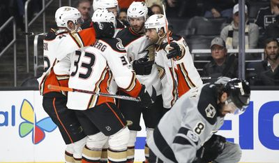 Anaheim Ducks players celebrate a goal by Andrew Cogliano as Los Angeles Kings' Drew Doughty, foreground, kneels on the ice during the first period of an NHL hockey game Saturday, Feb. 25, 2017, in Los Angeles.(AP Photo/Jae C. Hong)