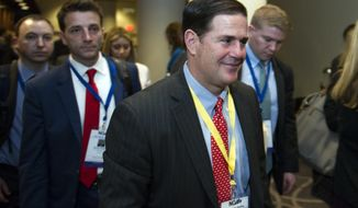 Arizona Gov. Doug Ducey, center right, leaves a Governors lunch, with his staff, during the National Governors Association Winter Meeting in Washington, Saturday, Feb. 25, 2017. (AP Photo/Cliff Owen)