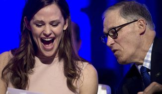 Actress Jennifer Garner and National Governors Association (NGA) Vice Chairman Washington Gov. Jay Inslee look at a document following Garner's address to the NGA's Winter Meeting in Washington, Saturday, Feb. 25, 2017. Garner spoke about the need for early educaiton. (AP Photo/Cliff Owen)