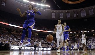 Kansas guard Devonte' Graham (4) reacts after he scored over Texas guard Eric Davis Jr. (10) during the first half of an NCAA college basketball game, Saturday, Feb. 25, 2017, in Austin, Texas. (AP Photo/Eric Gay)
