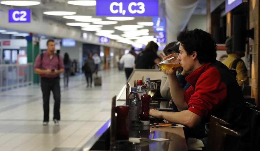 In this photo made Friday, Feb. 24, 2017, traveler Dominic Maley sips on a beer while waiting to board a flight at St. Louis Lambert International Airport in St. Louis. The Missouri House has passed a proposal that would allow people to bring alcohol out of airport bars and restaurants to gates. (AP Photo/Jeff Roberson)
