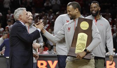 Former Maryland coach Gary Williams, left, embraces former player Byron Mouton at a ceremony to honor the team's 15th anniversary of its NCAA title run, during halftime of an NCAA college basketball game between Maryland and Iowa, Saturday, Feb. 25, 2017, in College Park, Md. (AP Photo/Patrick Semansky)