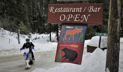 ADVANCE FOR SATURDAY FEB. 25 AND THEREAFTER - In a Feb. 10, 2017 photo, a snow machine rider passes a restaurant at Priest Lake, Idaho. Relentless snowfall has smothered Priest Lake this winter, and snowmobilers are loving it. (Rich Landers/The Spokesman Review via AP)