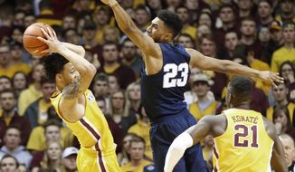Minnesota's Amir Coffey, left, keeps the ball away from Penn State's Josh Reaves, center, during the first half of an NCAA college basketball game Saturday, Feb. 25, 2017, in Minneapolis. (AP Photo/Jim Mone)