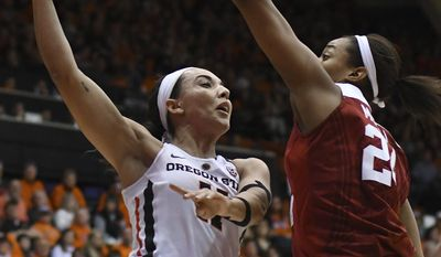 Oregon State guard Gabriella Hanson (11) makes a pass around Stanford forward Erica McCall (24) during the first half of an NCAA college basketball game Friday, Feb. 24, 2017, in Corvallis, Ore. (Anibal Ortiz/Corvallis Gazette-Times via AP)