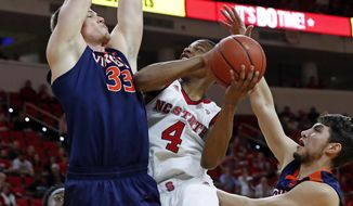 North Carolina State 's Dennis Smith Jr. (4) challenges Virginia's Jack Salt (33) and Ty Jerome (11) during the first half of an NCAA college basketball game in Raleigh, N.C., Saturday, Feb. 25, 2017. (AP Photo/Karl B DeBlaker)