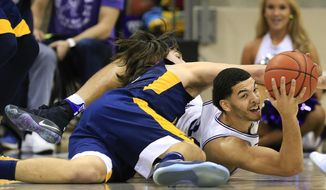 TCU  guard Kenrich Williams, right, fights off West Virginia forward Nathan Adrian, left, to come up with a loose ball in the first half of an NCAA college basketball game, Saturday, Feb. 25, 2017, in Fort Worth, Texas. (AP Photo/Ron Jenkins)