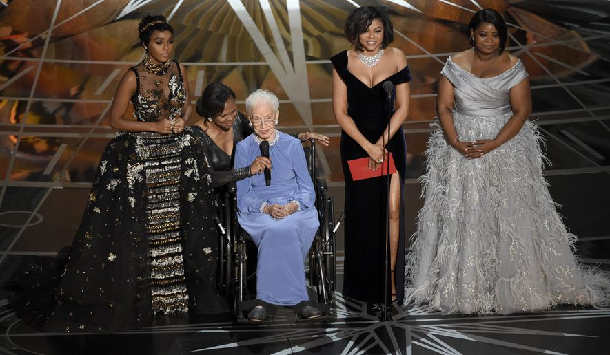 """Janelle Monae, left, Taraji P. Henson, second right and Octavia Spencer, right, introduce Katherine Johnson, seated, the inspiration for """"Hidden Figures,"""" as they present the award for best documentary feature at the Oscars on Sunday, Feb. 26, 2017, at the Dolby Theatre in Los Angeles. (Photo by Chris Pizzello/Invision/AP)"""