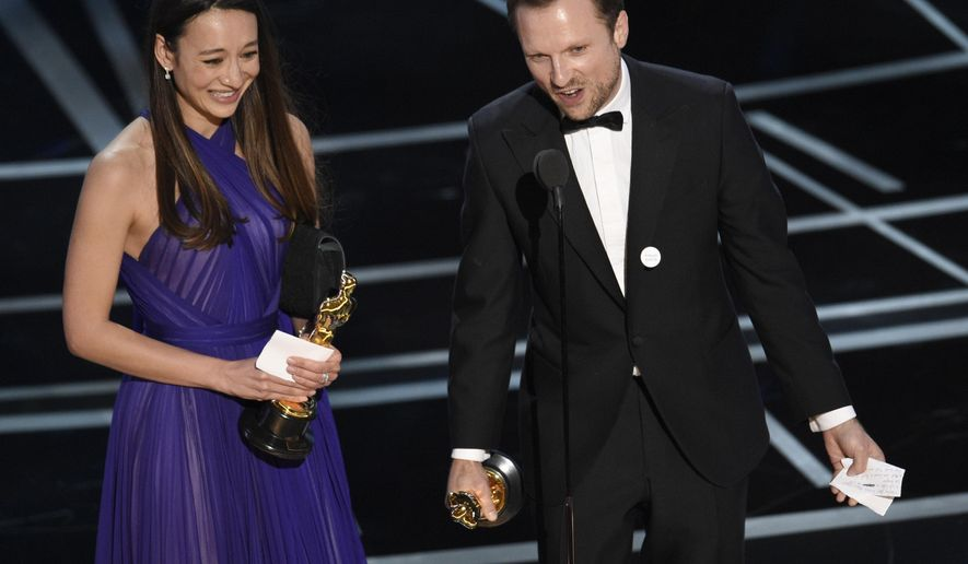 """Joanna Natasegara, left, and Orlando von Einsiedel accept the award for best documentary short subject for """"The White Helmets"""" at the Oscars on Sunday, Feb. 26, 2017, at the Dolby Theatre in Los Angeles. (Photo by Chris Pizzello/Invision/AP)"""