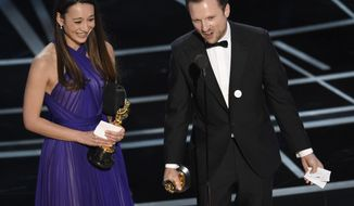 "Joanna Natasegara, left, and Orlando von Einsiedel accept the award for best documentary short subject for ""The White Helmets"" at the Oscars on Sunday, Feb. 26, 2017, at the Dolby Theatre in Los Angeles. (Photo by Chris Pizzello/Invision/AP)"