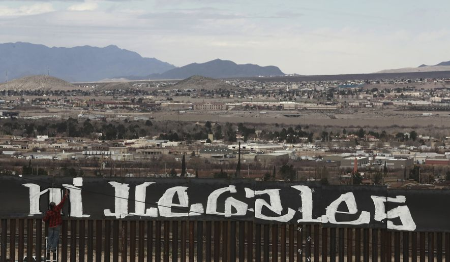 "Sunland Park, New Mexico, is seen over the U.S. border fence as a protestor finishes painting the Spanish slogan ""Neither delinquents nor illegals, we are international workers"" on the Ciudad Juarez, Mexico side of the fence, Sunday, Feb. 26, 2017. A group of around 30 protestors gathered to paint messages on the border wall on the outskirts of Ciudad Juarez and stage a performance mocking the relationship between Presidents Donald Trump and Enrique Pena Nieto. (AP Photo/Christian Torres)"