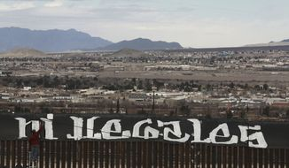 """Sunland Park, New Mexico, is seen over the U.S. border fence as a protestor finishes painting the Spanish slogan """"Neither delinquents nor illegals, we are international workers"""" on the Ciudad Juarez, Mexico side of the fence, Sunday, Feb. 26, 2017. A group of around 30 protestors gathered to paint messages on the border wall on the outskirts of Ciudad Juarez and stage a performance mocking the relationship between Presidents Donald Trump and Enrique Pena Nieto. (AP Photo/Christian Torres)"""