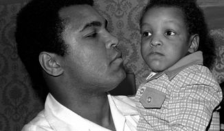FILE - In this April 15, 1975 file photo, Heavyweight boxing champion Muhammad Ali, and Little Muhammad Ali, his 2 1/2 year old son, arrive at Miami Beach, Fla. Muhammad Ali's son, who bears the boxing great's name, was detained by immigration officials at a Florida airport and questioned about his ancestry and religion in what amounted to unconstitutional profiling, a family friend said Saturday, Feb. 25, 2017. (AP Photo/File)