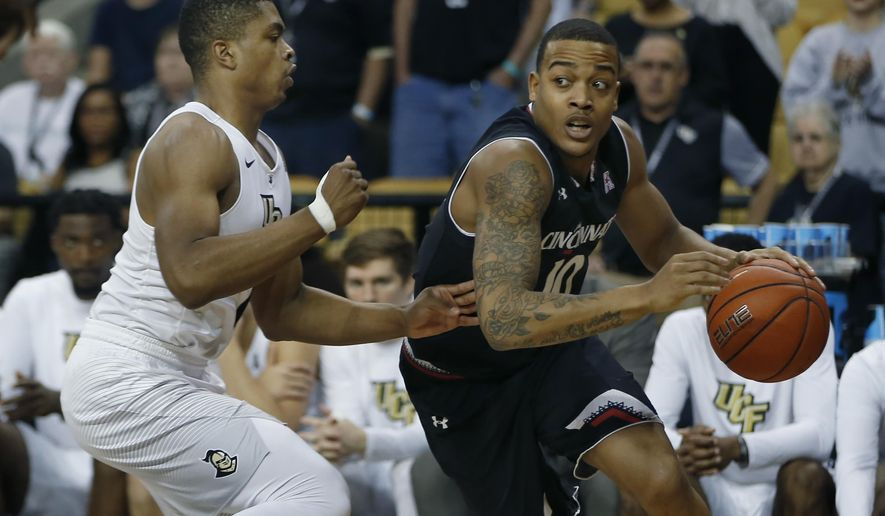 Cincinnati Bearcats guard Troy Caupain (10) drives around Central Florida guard B.J. Taylor (1) during the first half of an NCAA college basketball game in Orlando, Fla., on Sunday, Feb. 26, 2017. (AP Photo/Reinhold Matay)