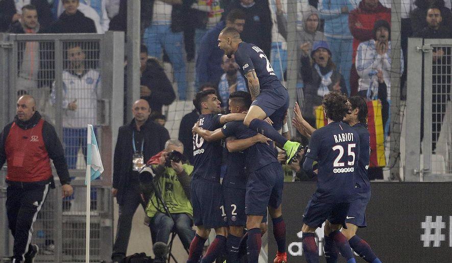 Paris Saint-Germain players celebrate after Paris scored, during the League One soccer match between Marseille and Paris Saint-Germain, at the Velodrome Stadium, in Marseille, southern France, Sunday, Feb. 26, 2017. (AP Photo/Claude Paris)