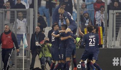 Paris Saint-Germain players celebrate after Paris scored, during the League One soccer match between Marseille and Paris Saint-Germain, at the Velodrome Stadium, in Marseille, southern France, Sunday, Feb. 26, 2017. (AP Photo/Claude Paris)