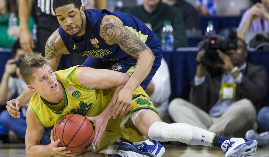 Notre Dame's Rex Pflueger, bottom, grabs a loose ball in front of Georgia Tech's Tadric Jackson during the first half of an NCAA college basketball game Sunday, Feb. 26, 2017, in South Bend, Ind. (AP Photo/Robert Franklin)