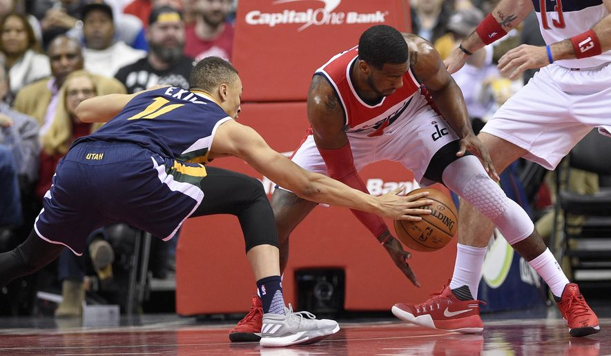Utah Jazz guard Dante Exum (11), of Australia, battles for the ball against Washington Wizards guard John Wall, right, during the first half of an NBA basketball game, Sunday, Feb. 26, 2017, in Washington. (AP Photo/Nick Wass)
