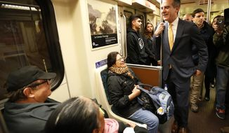 FILE - In this Dec. 6, 2016, file photo, Los Angels Mayor Eric Garcetti, right, talks to passengers aboard a Metro Red Line train that he boarded at the Universal City Red Line station in Los Angeles. Garcetti's toughest competitor in his campaign for a second term might not be another candidate. The mayor shares the ballot with a proposal intended to restrict large real estate projects that challenges his vision for building thousands of new apartments clustered around train stations. (Al Seib/Los Angeles Times via AP, Pool, File)