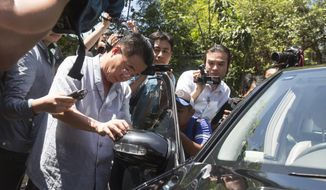 An employee of North Korean Embassy checks his car for damage outside the embassy building in Kuala Lumpur, Malaysia, Sunday, Feb. 26, 2017.  Investigation unleashed a serious diplomatic fight between Malaysia and North Korea, a prime suspect in the Feb. 13 killing of Kim Jong Nam at Kuala Lumpur's airport. (AP Photo/Alexandra Radu)
