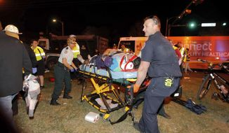 New Orleans emergency personnel attend to an injured parade watcher after a pickup truck plowed into a crowd injuring multiple people watching the Krewe of Endymion parade in the Mid-City section of New Orleans, Saturday, Feb. 25, 2017. Police Chief Michael Harrison says one person in custody and that he is being investigated for driving while intoxicated.  (Scott Threlkeld/The Advocate via AP)