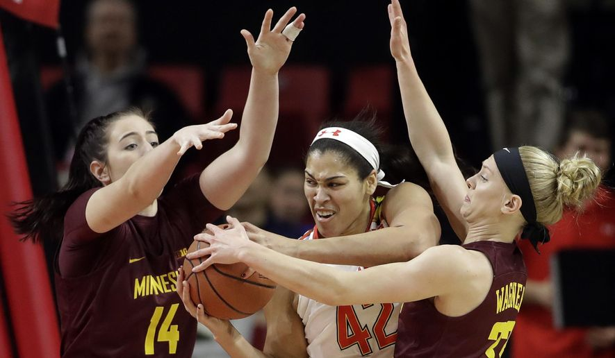 Maryland center Brionna Jones, center, drives between Minnesota center Bryanna Fernstrom, left, and guard Carlie Wagner in the first half of an NCAA college basketball game, Sunday, Feb. 26, 2017, in College Park, Md. (AP Photo/Patrick Semansky)