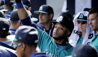 Seattle Mariners' Robinson Cano celebrates in the dugout after scoring when Tyler O'Neill was walked with the bases loaded during the third inning of a spring training baseball game against the San Diego Padres, Sunday, Feb. 26, 2017, in Peoria, Ariz. (AP Photo/Charlie Riedel)