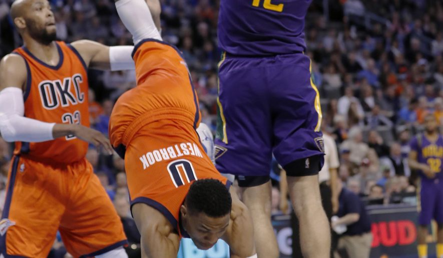 Oklahoma City Thunder guard Russell Westbrook (0) falls after fouling New Orleans Pelicans forward Donatas Motiejunas (12) during the first half of an NBA basketball game in Oklahoma City, Sunday, Feb. 26, 2017. (AP Photo/Alonzo Adams)