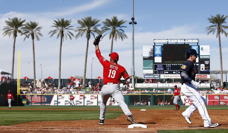Cleveland Indians left fielder Daniel Robertson, right, beats out an infield hit as Cincinnati Reds first baseman Joey Votto (19) reaches out for the late throw during the third inning of a spring training baseball game Saturday, Feb. 25, 2017, in Goodyear, Ariz. The Indians defeated the Reds 8-2. (AP Photo/Ross D. Franklin)