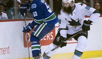 Vancouver Canucks center Bo Horvat (53) fights for control of the puck with San Jose Sharks defenseman Brent Burns (88) during first-period NHL  hockey game action Vancouver, British Columbia, Saturday, Feb 25, 2017. (Jonathan Hayward/The Canadian Press via AP)