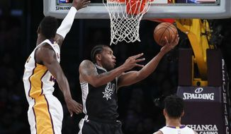 San Antonio Spurs' Kawhi Leonard, center, puts up a shot past Los Angeles Lakers' Julius Randle during the first half of an NBA basketball game, Sunday, Feb. 26, 2017, in Los Angeles. (AP Photo/Jae C. Hong)
