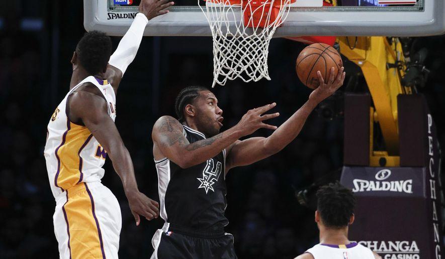 San Antonio Spurs' Kawhi Leonard, center, puts up a shot past Los Angeles Lakers' Julius Randle during the first half of an NBA basketball game, Sunday, Feb. 26, 2017, in Los Angeles. (AP Photo/Jae C. Hong)