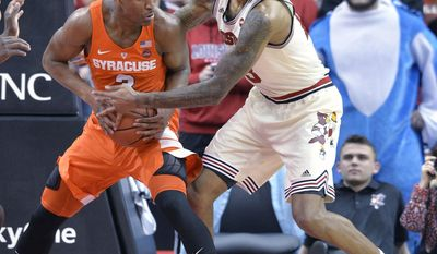 Louisville's Ray Spalding (13) attempts to strip the ball from Syracuse's Andrew White III (3) during the first half of an NCAA college basketball game, Sunday, Feb. 26, 2017, in Louisville, Ky. (AP Photo/Timothy D. Easley)