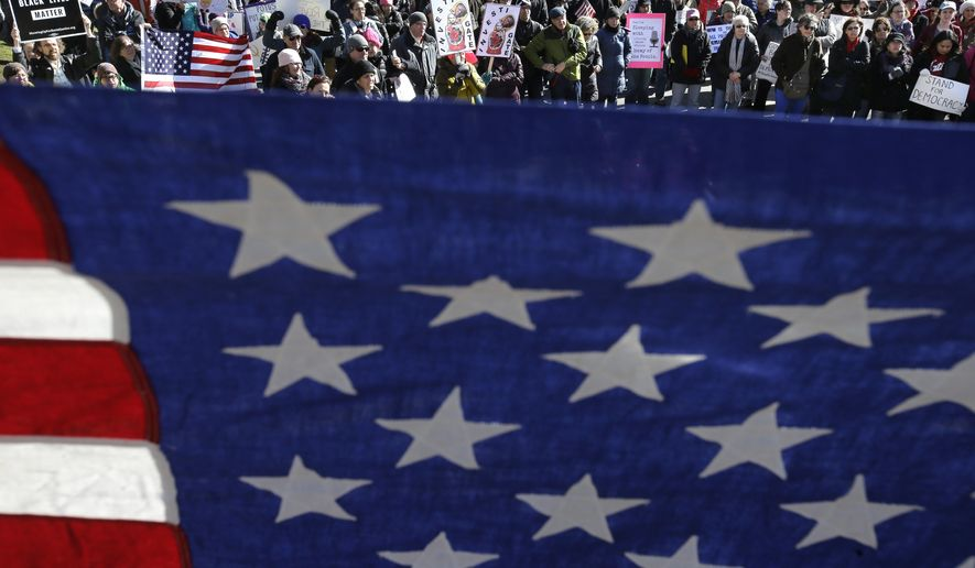 """An American flag is held in front of protesters holding placards and chanting slogans during a demonstration called """"Emergency Rally to Stand for Democracy,"""" Sunday, Feb. 26, 2017, in Boston. Demonstrators called for an investigation into what they describe as the possible involvement of Russian officials in the campaign of then presidential candidate Donald Trump in the Nov. 2016 election. (AP Photo/Steven Senne)"""