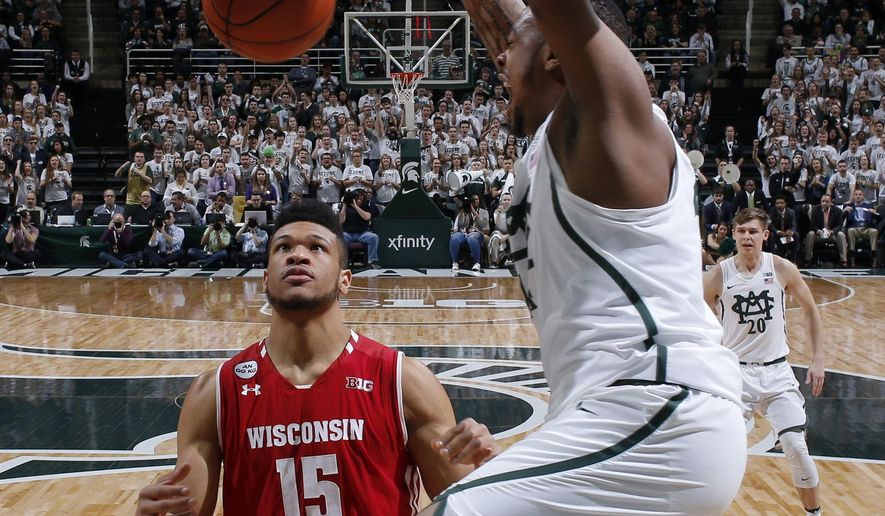 Michigan State's Nick Ward, right, dunks over Wisconsin's Charles Thomas (15) during the first half of an NCAA college basketball game, Sunday, Feb. 26, 2017, in East Lansing, Mich. (AP Photo/Al Goldis)