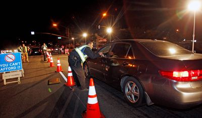 In this Dec. 16, 2011 photo, police officers check drivers at a sobriety checkpoint in Escondido, Calif. Starting Jan. 1, 2012, police in California can no longer impound vehicles from DUI checkpoints when the driver's only offense is driving without a license. The impounds have been controversial where critics say they are used to drive out illegal immigrants. The American Civil Liberties Union has questioned how much Escondido is making from illegal immigrants whose cars are impounded because they do not have drivers licenses.  (AP Photo/Lenny Ignelzi)