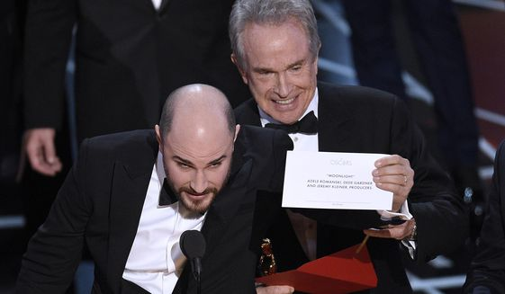 "Jordan Horowitz, producer of ""La La Land,"" shows the envelope revealing ""Moonlight"" as the true winner of best picture at the Oscars on Sunday, Feb. 26, 2017, at the Dolby Theatre in Los Angeles. Presenter Warren Beatty looks on from right. (Photo by Chris Pizzello/Invision/AP)"
