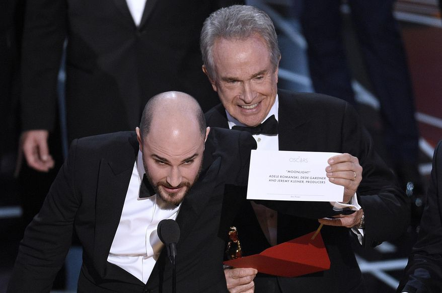 """Jordan Horowitz, producer of """"La La Land,"""" shows the envelope revealing """"Moonlight"""" as the true winner of best picture at the Oscars on Sunday, Feb. 26, 2017, at the Dolby Theatre in Los Angeles. Presenter Warren Beatty looks on from right. (Photo by Chris Pizzello/Invision/AP)"""