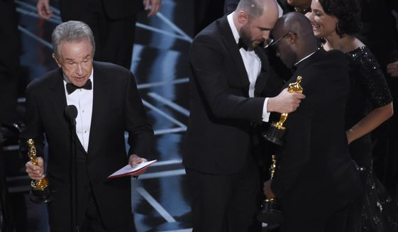 """Warren Beatty, from left, reveals """"Moonlight"""" as the actual winner of best picture as Jordan Horowitz embraces Barry Jenkins at the Oscars on Sunday, Feb. 26, 2017, at the Dolby Theatre in Los Angeles. (Photo by Chris Pizzello/Invision/AP)"""