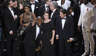 "Barry Jenkins, foreground left, and the cast accept the award for best picture for ""Moonlight"" at the Oscars on Sunday, Feb. 26, 2017, at the Dolby Theatre in Los Angeles. (Photo by Chris Pizzello/Invision/AP)"
