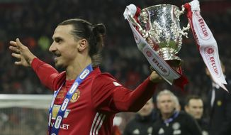 Manchester United's Zlatan Ibrahimovic holds the trophy after Manchester won the English League Cup final soccer match between Manchester United and Southampton FC at Wembley stadium in London, Sunday, Feb. 26, 2017. (AP Photo/Tim Ireland)