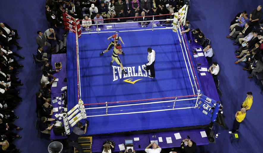 In this Feb. 24, 2017 photo, Midshipman Zoe Wang, in red, of Herndon, Va., punches Ally Annick of Pasadena, Calif., in a 132-lb boxing match during the U.S. Naval Academy's Brigade Boxing Championships in Annapolis, Md. Since the first championship in 1942, it's become one of the most popular events at the Naval Academy. (AP Photo/Patrick Semansky)
