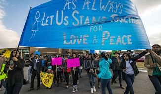 Hundreds of people march for peace on Sunday, Feb. 26, 2017, around the Ball Conference Center in Olathe, Kan., before starting a prayer vigil in response to the deadly shooting Wednesday. Adam Purinton was arrested hours after the attack and accused of shooting two Indian immigrants and a third man at a bar, in what some believe was a hate crime. (Allison Long/The Kansas City Star via AP)