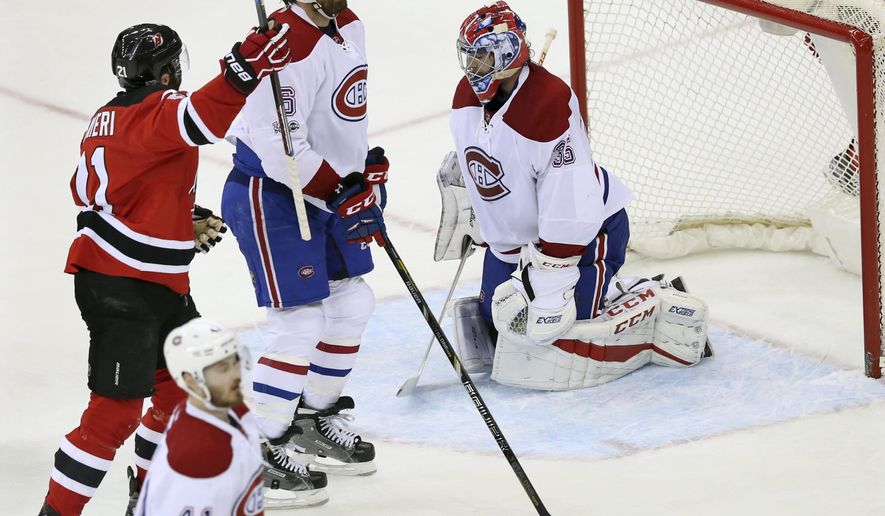 New Jersey Devils right wing Kyle Palmieri (21) raises his arm after scoring a goal against Montreal Canadiens goalie Al Montoya (35) during the first period of an NHL hockey game, Monday, Feb. 27, 2017, in Newark, N.J. (AP Photo/Mel Evans)