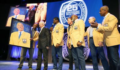 Former Dallas Cowboys, from left to right, Charles Haley shows a painted portrait of Hall of Fame owner Jerry Jones to Jones, Michael Irvin, Troy Aikman, Emmitt Smith, Roger Staubach and Tony Dorsett during the 25th Anniversary of Super Bowl XXVII at Gilley's in Dallas, Saturday, Feb. 25, 2017. (Tom Fox/The Dallas Morning News via AP)