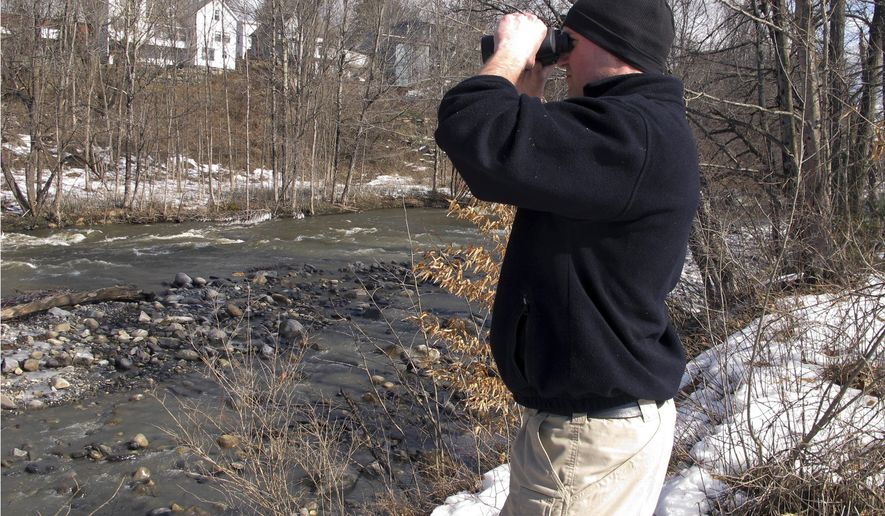 Vermont State Police Trooper John Bruzzi searches the Winooski River Monday, Feb. 27, 2017, in Plainfield, Vt., for signs of a woman who disappeared after a weekend car crash. Police say Krystal Bailey, 29, of Barre, Vermont, was a passenger in a car that went out of control and hit a guardrail Saturday night.   (AP Photo/Lisa Rathke)