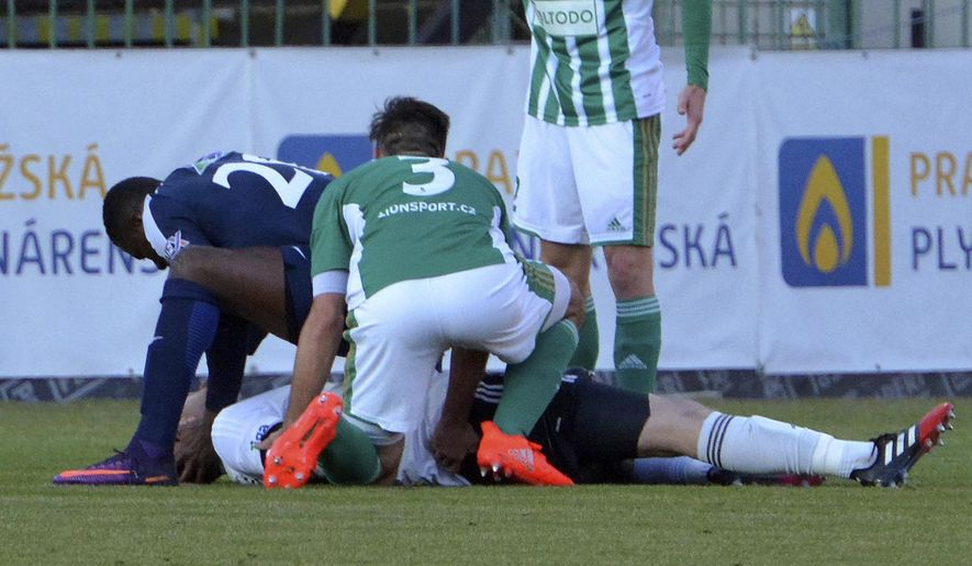 In this picture taken on Saturday, Feb. 25, 2017, Slovacko's striker Francis Kone, left, helps Bohemians' goalkeeper Martin Berkovec, down, during their Czech Republic's first division match played in Prague. Kone reacted quickly and helped to save life of Berkovec after he had a collision with a teammate. (bohemians.cz via AP)